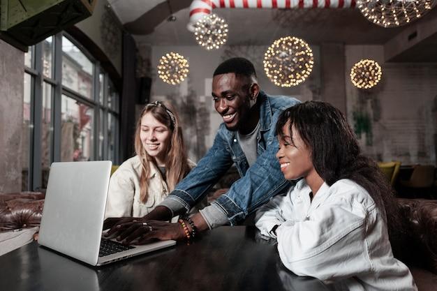 Adoráveis amigos olhando para laptop dentro de casa