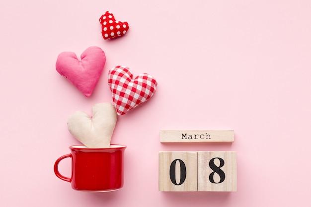 Adoráveis corações no fundo rosa com letras de 8 de março