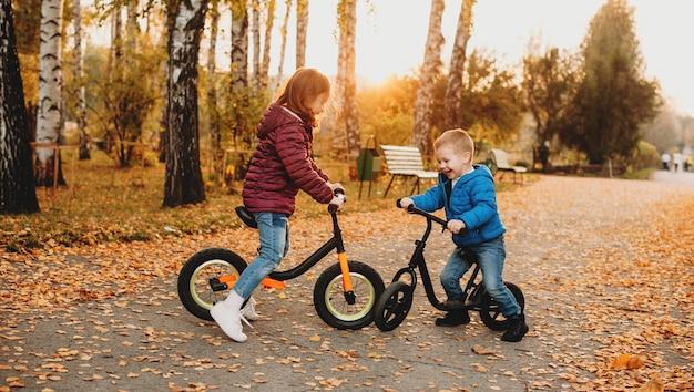 Adoráveis crianças brancas vestidas de jeans, andando de bicicleta no parque