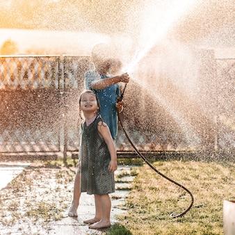 Adoráveis crianças brincando com uma mangueira de jardim em um dia quente e ensolarado de verão no pôr do sol
