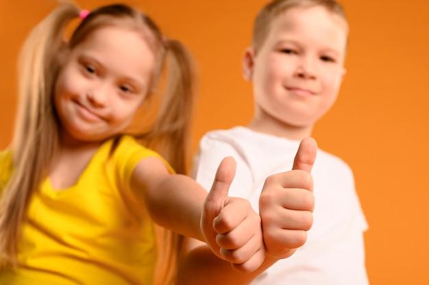 Adoráveis crianças com polegares para cima