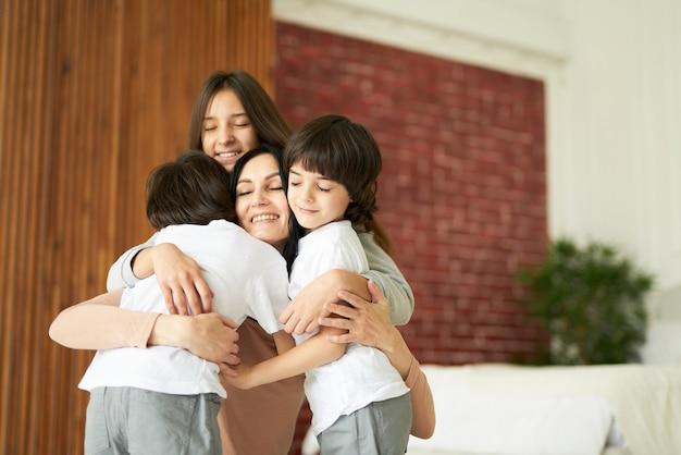 Adoráveis crianças latinas, adolescente e dois meninos gêmeos abraçando sua mãe enquanto se divertem juntos dentro de casa. mãe brincando com os filhos em casa. família, conceito de paternidade