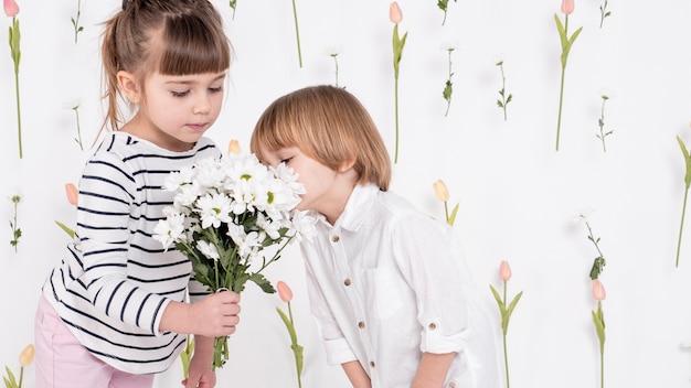 Adoráveis crianças olhando para o buquê de flores
