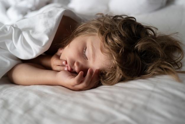 Adoráveis crianças pequenas descansam dormindo, desfrutam de um bom sono ou cochilo saudável e tranquilo. criança de seis anos dormindo na cama.