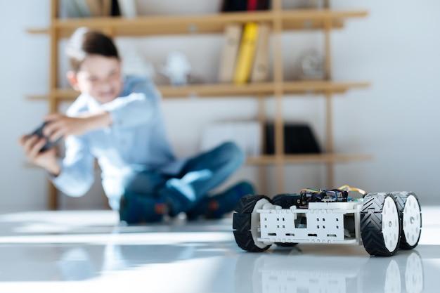 Adoráveis crianças pré-adolescentes inspecionando oficina de veículos robóticos