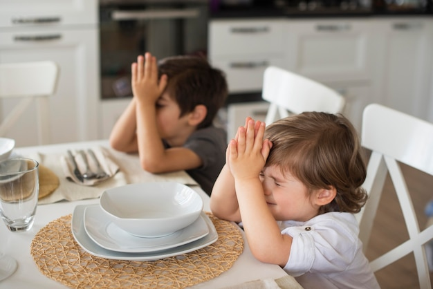 Adoráveis crianças rezando em casa