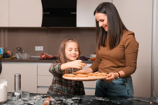 Adoráveis duas meninas, uma mãe e sua filha estão fazendo biscoitos de natal juntas na cozinha