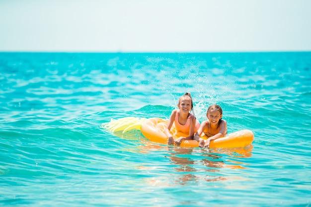 Adoráveis garotinhas se divertindo na praia nas ondas, nadando e nadando