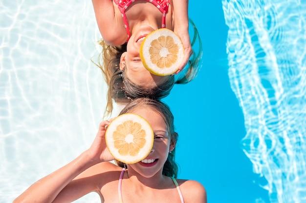 Adoráveis irmãzinhas brincam na piscina ao ar livre