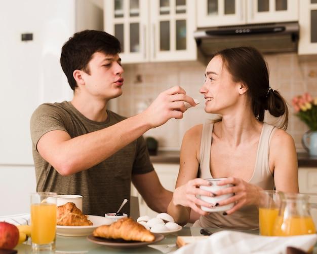 Adoráveis jovens amantes tomando café da manhã