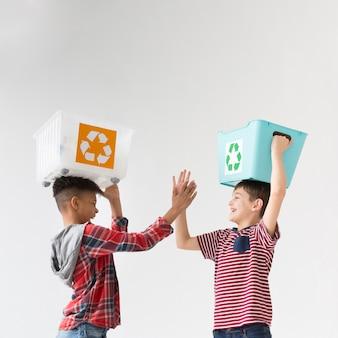Adoráveis jovens rapaz segurando caixas de reciclagem
