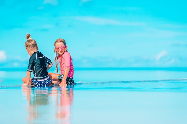 Adoráveis meninas brincando na piscina de férias