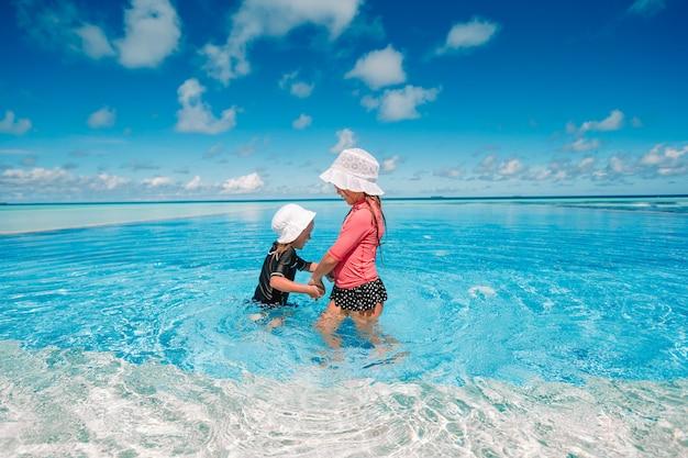 Adoráveis meninas brincando na piscina