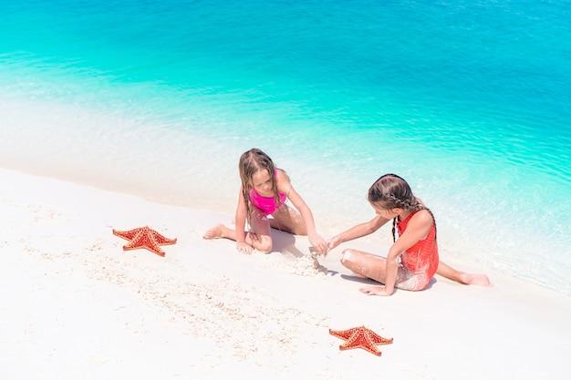 Adoráveis meninas com estrela do mar na praia vazia branca