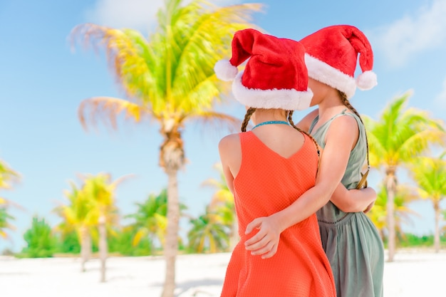 Adoráveis meninas de chapéu de papai noel durante as férias de praia se divertem juntos