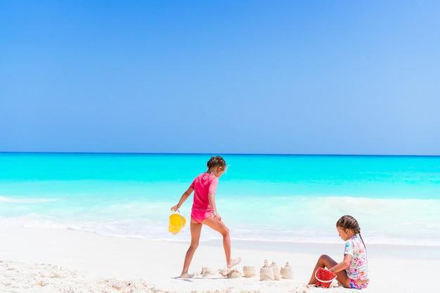 Adoráveis meninas durante as férias de verão. crianças brincando com brinquedos de praia na praia branca