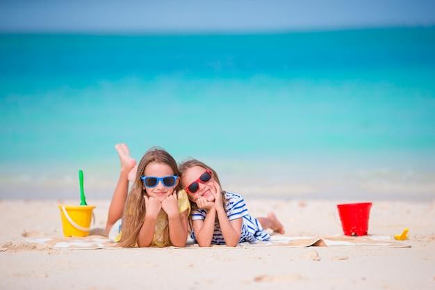Adoráveis meninas durante as férias de verão. crianças com brinquedos de praia na praia branca