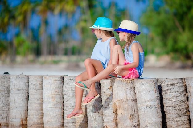 Adoráveis meninas durante as férias de verão na praia branca