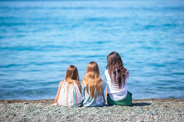 Adoráveis meninas e jovem mãe em uma praia tropical de areia branca