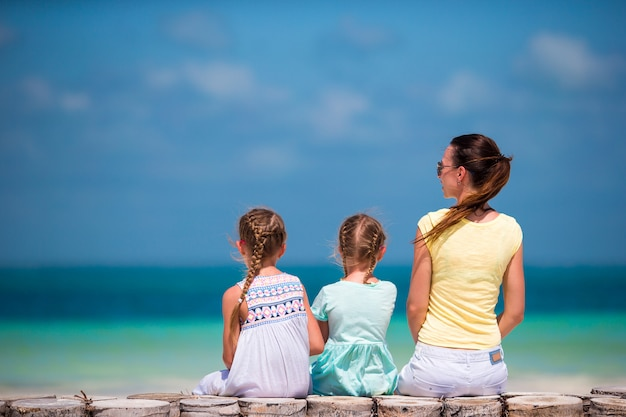 Adoráveis meninas e jovem mãe na praia tropical branca