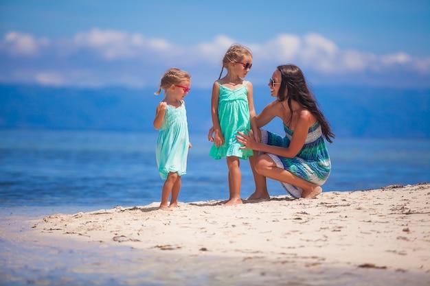 Adoráveis meninas e jovem mãe se divertir na praia branca tropical na ilha deserta