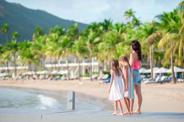 Adoráveis meninas e jovens mãe na praia branca em resort de luxo