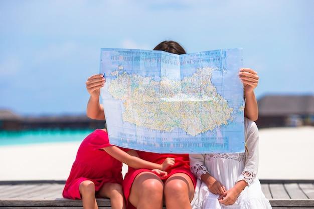 Adoráveis meninas e mãe com mapa da ilha na praia