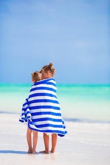 Adoráveis meninas embrulhadas na toalha na praia tropical