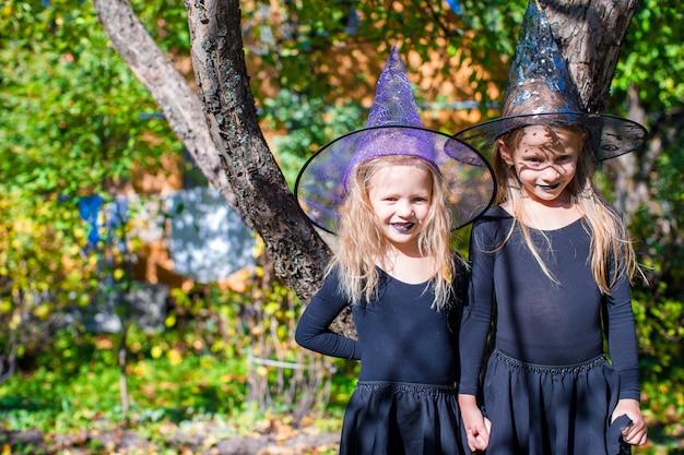 Adoráveis meninas na fantasia de bruxa no dia das bruxas ao ar livre