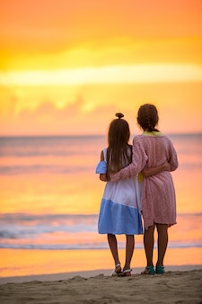 Adoráveis meninas na praia com belo pôr do sol colorido