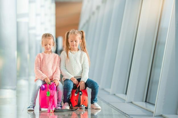 Adoráveis meninas no aeroporto com sua bagagem à espera de embarque