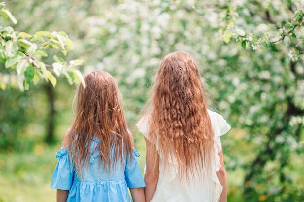 Adoráveis meninas no jardim de macieira florescendo na primavera