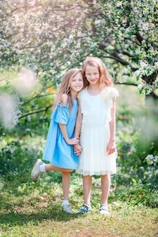 Adoráveis meninas no jardim de macieiras florescendo na primavera