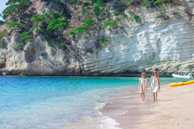 Adoráveis meninas se divertem juntos na praia tropical branca