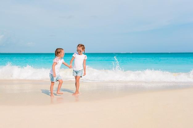 Adoráveis meninas se divertem muito na praia.