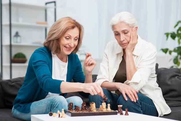 Adoráveis mulheres jogando xadrez juntos