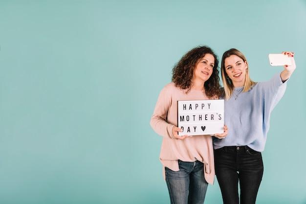 Adoráveis mulheres posando para selfie com saudação de dia das mães