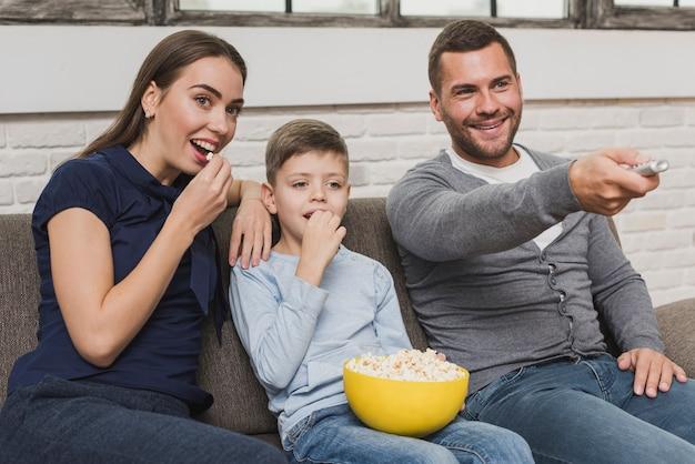 Adoráveis pais com o filho assistindo a um filme