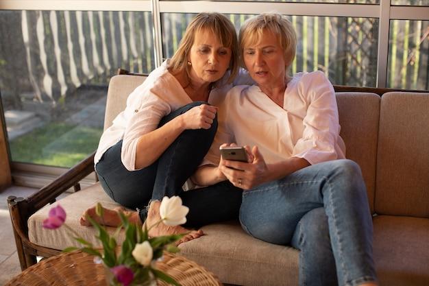 Adoráveis senhoras de 55 anos de idade usam smartphone para fazer compras online, sentadas no sofá à mesa com flores no pátio de uma casa de madeira