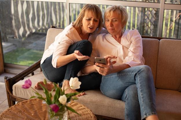 Adoráveis senhoras de 55 anos usam smartphone para discutir moda feminina, sentadas no sofá à mesa com flores no pátio de uma casa de madeira