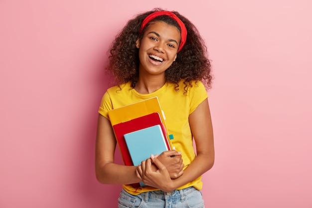 Adorável adolescente com cabelo encaracolado posando em uma camiseta amarela