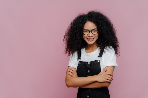 Adorável adolescente com corte de cabelo afro, mantém os braços cruzados, usa óculos, camiseta branca e macacão preto