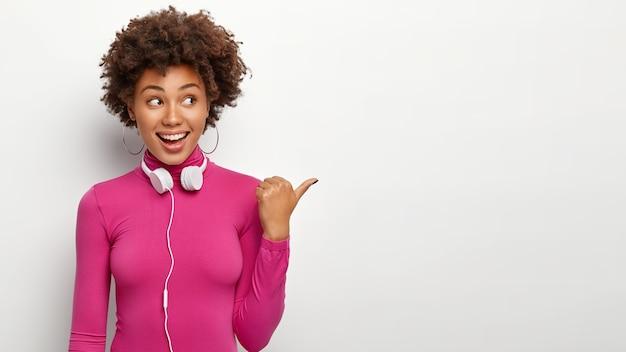 Adorável adolescente de pele escura com cabelo afro encaracolado, aparência feliz