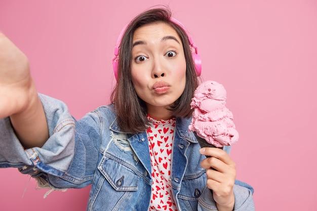 Adorável adolescente feminina romântica com aparência oriental segura um grande cone de sorvete, estende o braço para fazer selfie, usa fones de ouvido e ouve música vestida com uma jaqueta jeans isolada sobre a parede rosa