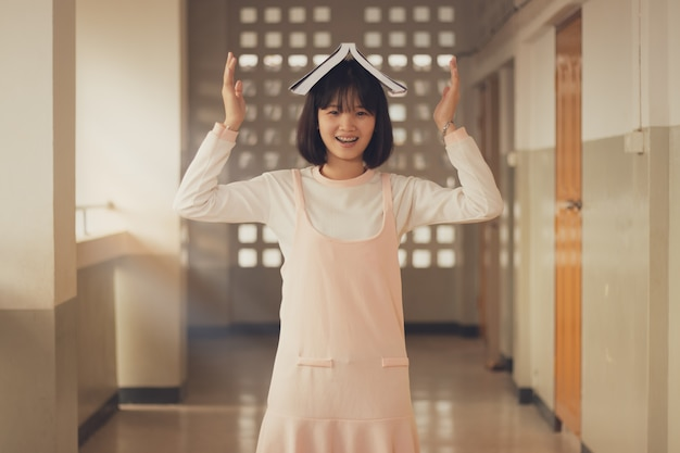 Adorável adolescente, menina lendo livro com diversão e feliz no tempo livre.