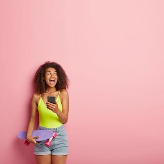 Adorável adolescente radiante com cabelo afro espesso, segurando um telefone celular