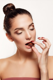 Adorável adolescente sorridente comendo chocolate