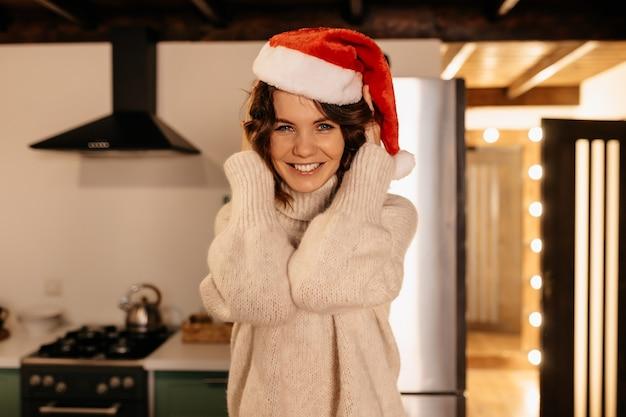 Adorável adorável jovem europeia com chapéu de papai noel, sentada na cozinha e posando