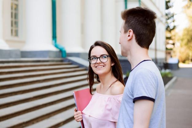 Adorável aluna com sorriso lindo olha para o namorado e indo para as aulas. dois estudantes apaixonados participando de palestras de uma universidade convencional