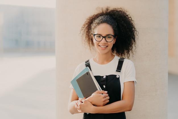 Adorável aluna de cabelos cacheados veste camiseta casual branca e macacão, detém o bloco de notas ou livro
